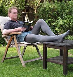 Mann in grauer Srumpfhose sitzt im Garten